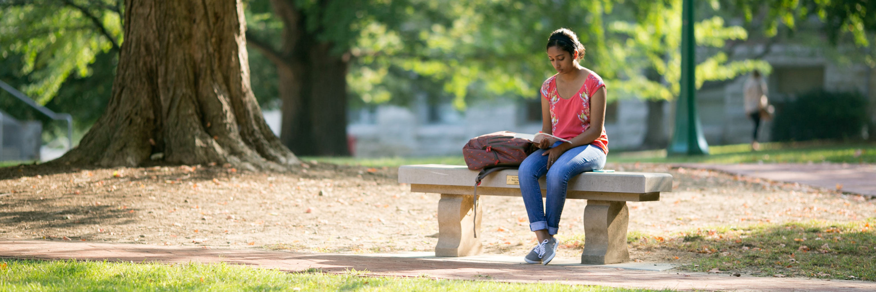 A girl sitting on a bench reading